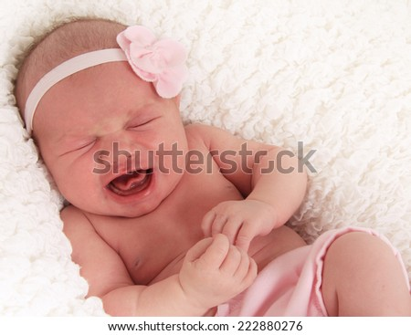 One week old newborn baby girl crying loudly.  - stock photo