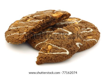 one whole and a broken chocolate chip cookie with nuts decorated with white chocolate on a white background - stock photo