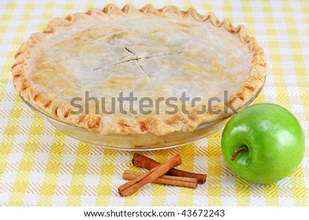 One whole homemade apple pie with cinnamon sticks and a granny smith apple. - stock photo