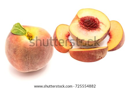 One whole peach with green leaf, one half with stone, three slices around, isolated on white background