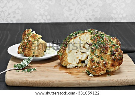 One whole roasted cauliflower head with a slice removed revealing inside appearance. - stock photo