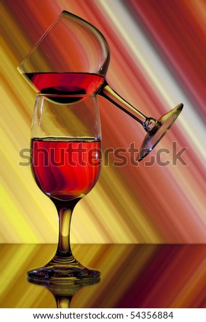 One wine glass balanced on another with colorful background - stock photo