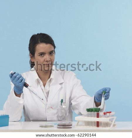 one woman scientiest sitting down while working on experiment, front view, colored background real laboratory equipement - stock photo