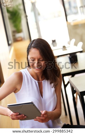 One woman sitting at cafe smiling at computer tablet