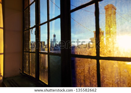 One World Trade Center (aka Freedom Tower) and Lower Manhattan skyline seen through defocused window back lit by afternoon yellow sun on a rooftop West Village apartment. - stock photo