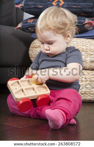 one year age blonde lovely cute caucasian white baby grey shirt pink trousers and shocks playing with wheel wooden colors toys indoor on brown floor - stock photo