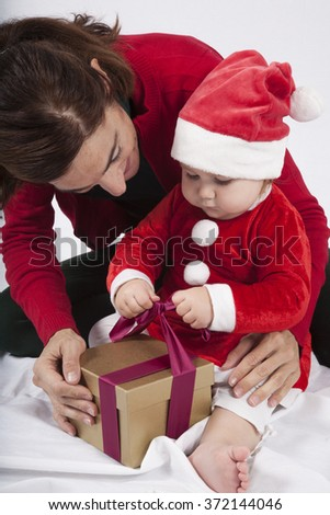 one year age caucasian blonde baby Santa Claus disguise with brunette woman mother red cardigan green trousers opening golden box gift Christmas on white background - stock photo