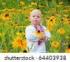 One year boy in folk shirt staying in the field of yellow flowers. - stock photo