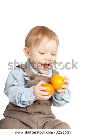 One year boy with tangerines in hands - stock photo