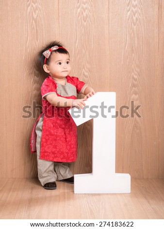 One year old Asian baby girl standing on floor with 1 wooden letter, Happy Birthday letter on background, little pretty asian girl smiling - stock photo