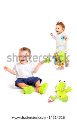 One year old babies (a boy and a girl) enjoy playing with toys. Studio Shot. All toys visible on the photo are officially property released.
