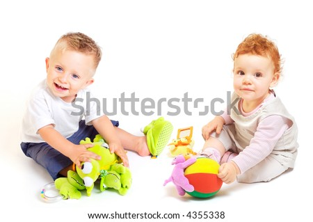 One year old babies (a boy and a girl) enjoy playing with toys. Studio Shot. All toys visible on the photo are officialy property released. - stock photo