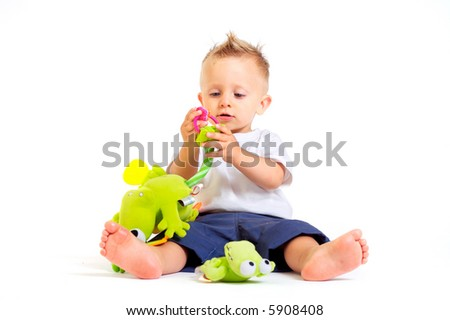 One year old baby boy enjoys playing with toys. Studio Shot. All toys visible on the photo are officially property released. - stock photo