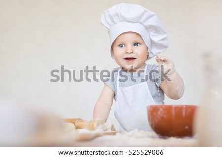 One year old baby boy in a suit of the cook surprised and smiling in the kitchen. Small kid as a little cook or scullion make pizza in chef suit. Cooking child lifestyle concept. Toddler playing