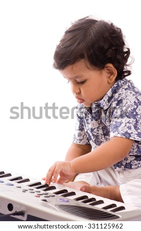 One year old baby boy playing with piano toy isolated on white background Mumbai, Maharashtra, India, Southeast Asia.