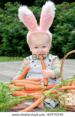One year old baby dressed in bunny ears, holding and eating a carrot; basket with carrot - stock photo