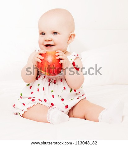 one year old baby eating an apple, in bed at home - stock photo