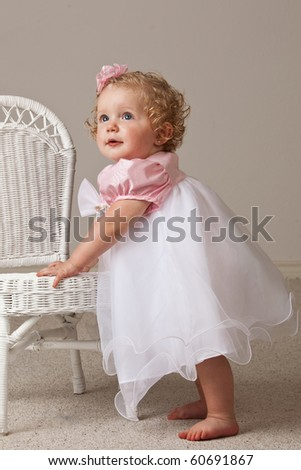 One year old baby girl in white and pink dress standing next to a white wicker chair. - stock photo
