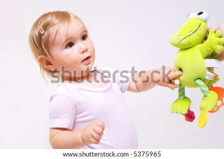 One year old baby girl with baby stroller. Studio Shot. All toys visible on the photo are officially property released.