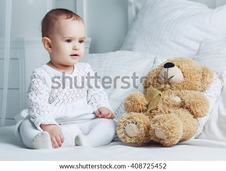 one year old baby in bed at home with a toy - stock photo