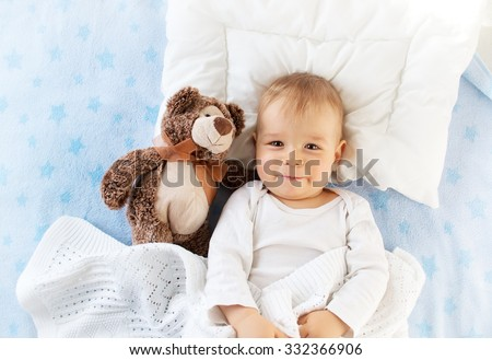 One year old baby lying in bed with a plush teddy bear - stock photo