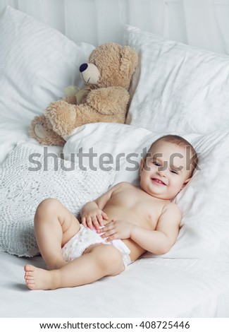 one year old baby wearing diapers in bed at home