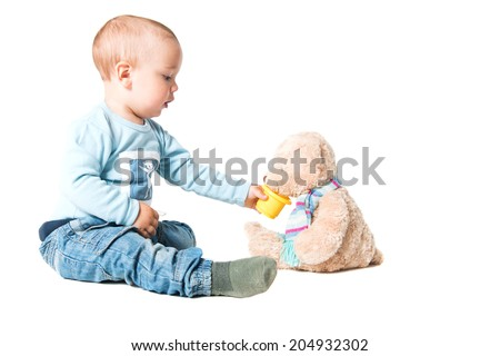 one year old boy feeding his teddy bear, isolated over white background  - stock photo