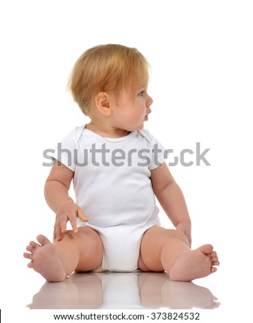 One year old child baby girl in diaper sitting looking at the corner isolated on a white background - stock photo