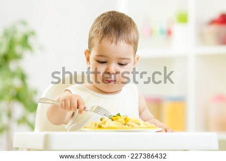one year old child boy in a highchair for feeding with a fork and a plate at home - stock photo