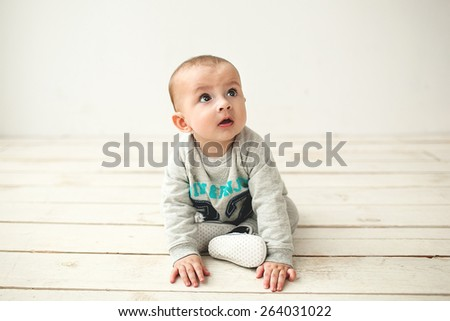 One year old cute baby boy sitting on rustic wooden floor over white background - stock photo