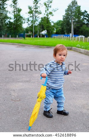 one year old European kid walking with a folded umbrella