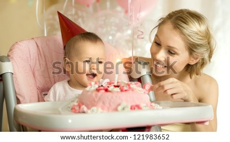 one-year-old little girl with  mammy solemnize birthday, happy laughter, horizontal photo - stock photo