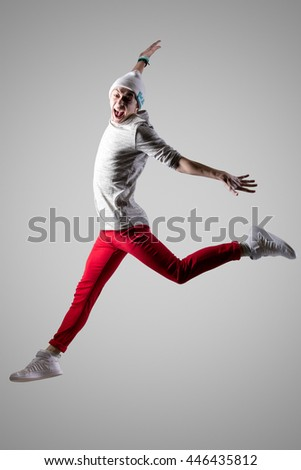 One young attractive modern style dancer guy in casual red jeans working out. Sporty excited person dancing and jumping with funny grimace. Full length photo on studio gray background - stock photo