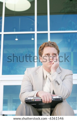 One young businessman sitting down holding laptop on his knees in front of office building with one hand on chin - stock photo