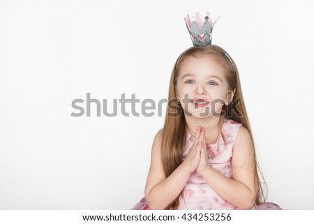 one young girl child begging looking up at viewer and hoping for something isolated on white background with copy space - stock photo