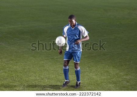One young male soccer player approaches the ball during a match - stock photo