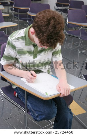 one young male student in a classroom sitting at his desk