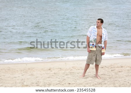one young man standing on the beach full length portrait