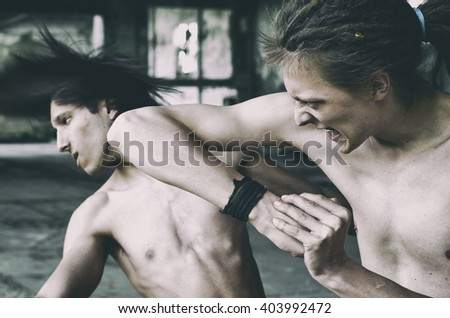 One young violent man elbow punching the other man in the face in city underworld. Cross processed image. - stock photo