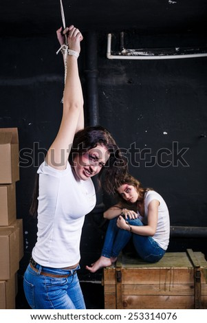 One young woman have fixed hands and hanging on rope another young woman sitting on wooden box  near dark wall. Crying. Hopelessness. - stock photo
