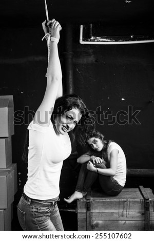 One young woman have fixed hands and hanging on rope another young woman sitting on wooden box near dark wall on black-and-white background. Crying. Hopelessness. - stock photo