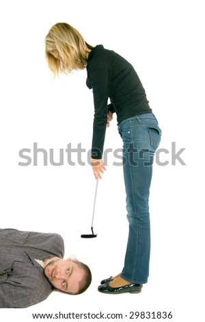 One young woman is trying to strike a ball with the golf club, a man is laying at her feet with this ball in his ear.