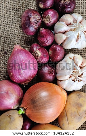 Onion, Potatoes and garlic on gunny background