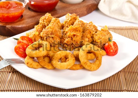 Onion rings and fried chicken - stock photo