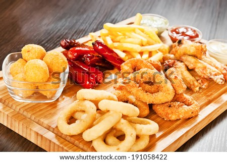 Onion rings, squid, chicken, deep-fried potato, hunter sausages and cheese  balls - stock photo