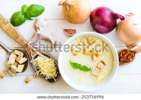 onion soup puree in a white plate with vegetables on the table - stock photo
