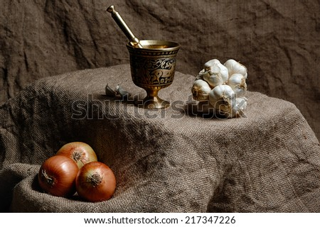 Onions and group of garlics with mortar and sack backgrounds - stock photo