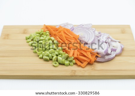 Onions, carrots and green beans. Basic vegetable for cooking. Chopped, sliced and cut vegetable on wooden chopping, a preparation of ingredients for cooking. - stock photo