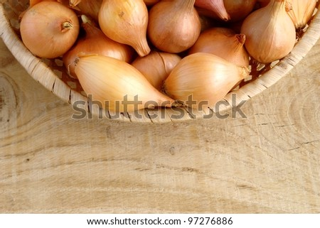 onions in a wicker basket on the board - stock photo