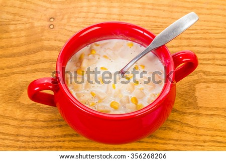 Onions, potatoes and whole grain corn in cream sauce for New England Corn Chowder.  Colorful stoneware mug on old wood tabletop.